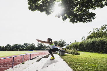 Young woman practicing in a track and field stadium - UUF008370