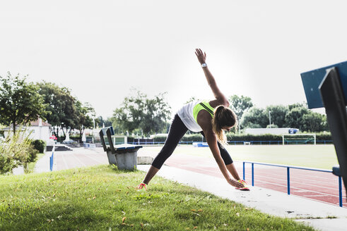 Young woman practicing in a track and field stadium - UUF008373