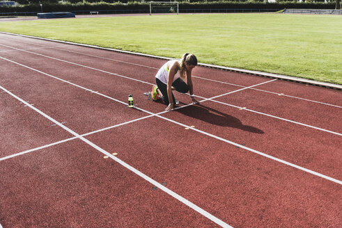 Young woman on tartan track in starting position - UUF008379