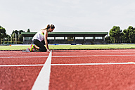 Young woman on tartan track in starting position - UUF008382