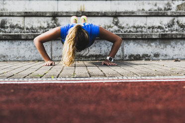 Young woman doing pushups on grandstand - UUF008388