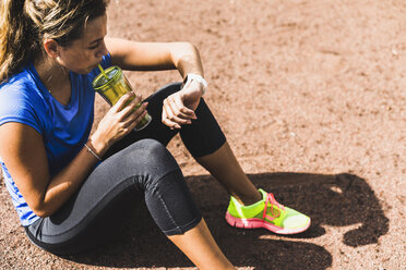 Sportive young woman sitting on sports field drinking from mug and looking at smartwatch - UUF008391