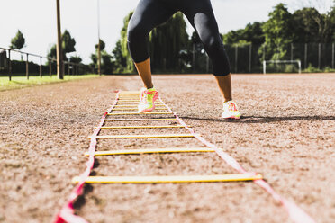 Young woman exercising on sports field with agility ladder - UUF008394