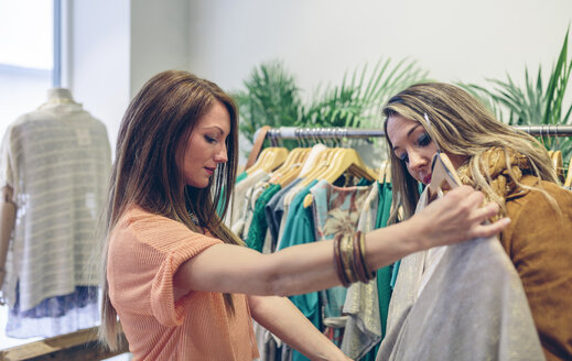 Two women shopping for clothes in a boutique - DAPF000320