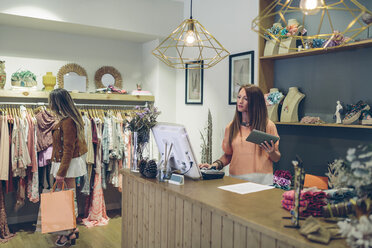 Shop assistant at counter in a boutique with customer shopping for clothes - DAPF000326