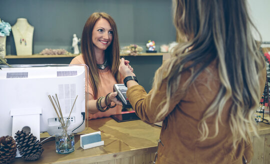 Woman paying using smartwatch with NFC technology in a store - DAPF000329