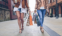 Low section of two women holding shopping bags walking in the city - DAPF000332