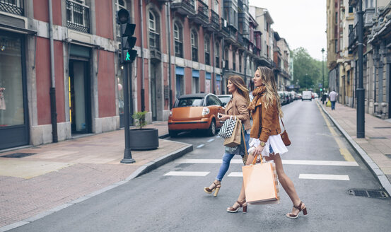 Two women holding shopping bags crossing the street in the city - DAPF000338