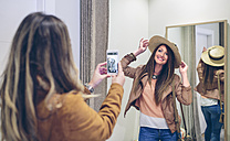 Woman taking picture of friend putting on straw hat in a boutique - DAPF000350