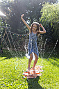 Girl having fun with inflatable water cushion in the garden - SARF002858