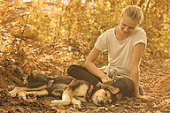 Young woman relaxing with her dog in nature - FCF001069