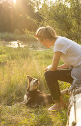 Young woman relaxing with her dog in nature at evening twilight - FCF001072