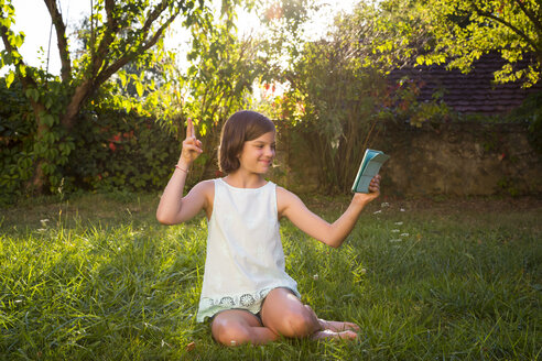 Girl sitting on a meadow taking selfie with tablet - LVF005278