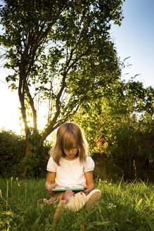 Little girl sitting on a meadow using tablet - LVF005284