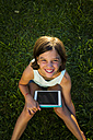 Portrait of smiling girl sitting on a meadow with tablet looking up to camera - LVF005287