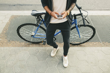 Teenager with a bike in the city, using smartphone - EBSF001730