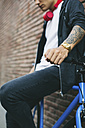 Teenager with a fixie bike, golden clock and tattoo on forearm - EBSF001748