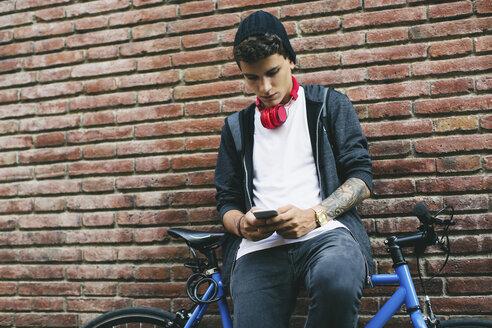 Teenager with a fixie bike, using smartphone - EBSF001751
