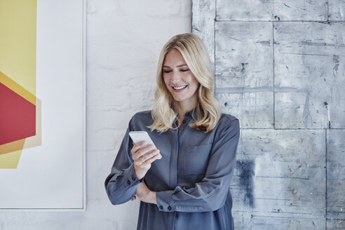 Smiling businesswoman looking at smartphone - RORF00268