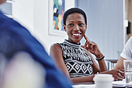 Smiling woman in a meeting looking at colleague - RORF00283