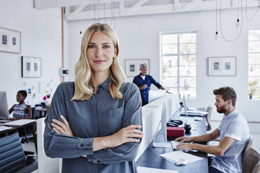 Portrait of confident businesswoman in office with staff in background - RORF00289