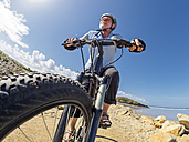 France, Brittany, senior man on electric mountainbike on coastal trail - LAF01717