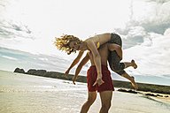 Playful teenage couple on the beach - UUF08413