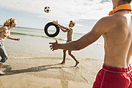 Friends playing with a ball and tyre on the beach - UUF08416