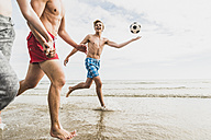 Friends running with a ball and tyre on the beach - UUF08422