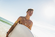 Teenage boy carrying surfboard at the sea - UUF08440