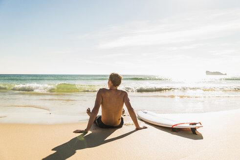 Teenage boy sitting on surfboard at the sea - UUF08443