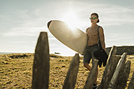 Young man carrying surfboard at the coast - UUF08452