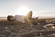 France, Bretagne, Crozon peninsula, woman lying on tree trunk, beach at sunset - UUF08470