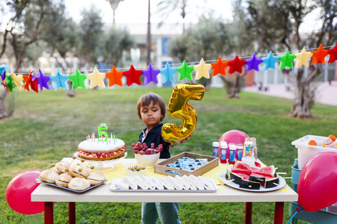 Little boy with golden balloon behind laid birthday table - VABF00771