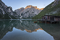 Italy, South Tyrol, Dolomites, Croda del Becco mountain and small wooden peir reflected in lake Braies at sunrise - LOMF00385