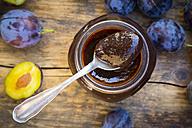 Tea spoon of plum jam on preserving jar and plums on wood - LVF05292