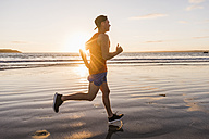 France, Crozon peninsula, jogger on the beach at sunset - UUF08486