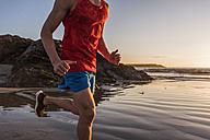 France, Crozon peninsula, jogger on the beach at sunset - UUF08489