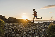 France, Crozon peninsula, jogger on the beach at sunset - UUF08492