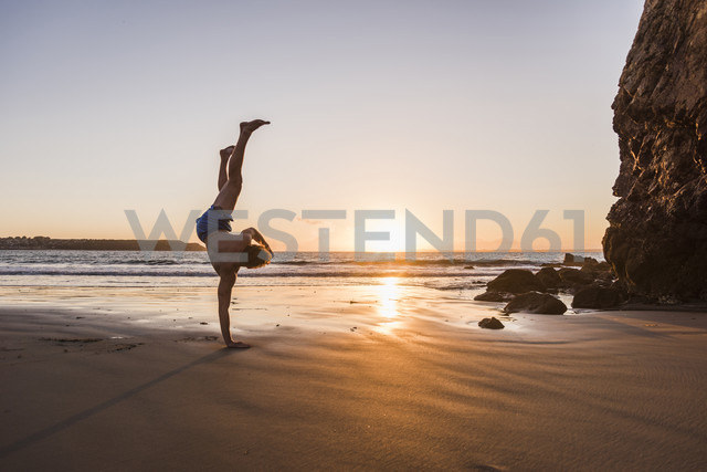 France, crozon peninsula, young man doing handstand on one arm at sunset - UUF08498