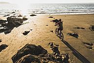 France, Crozon peninsula, Man biking on the beach - UUF08504