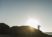 France, crozon peninsula, mountainbiker carrying his bike at sunset - UUF08507