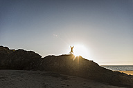France, crozon peninsula, mountainbiker lifting up his bike at sunset - UUF08510