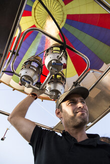 Man using burners of a hot air balloon - ABZF01226