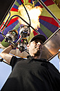 Man using burners of a hot air balloon - ABZF01232