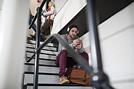 Young man with beanie and headphones sitting on stairs - ZEF10374