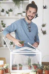Man putting cacti and succulents in a small greenhouse - RTBF00361