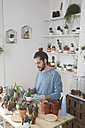 Young man transplanting cactus in his studio - RTBF00373