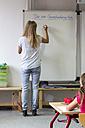 Back view of teacher writing on whiteboard - SARF02874