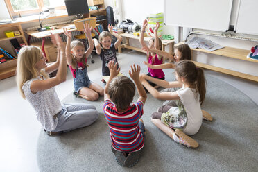 Teacher and pupils sitting in a circle on floor of their classroom raising hands - SARF02895